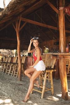 Junge und frau sitzen in authentischer strandbar mit einem kokosnussgetränk