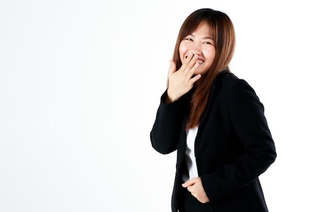 Junge und frische neue abgestufte aussehen asiatische geschäftsfrau in anzug pose mit handbedeckung mund beim lachen und humor auf weißem hintergrund fühlen.