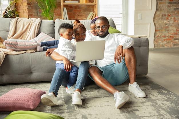 Junge und fröhliche afrikanische familie, die zu hause zeit miteinander verbringt. konzept des quarantäne-lebensstils, zusammengehörigkeit, wohnkomfort.
