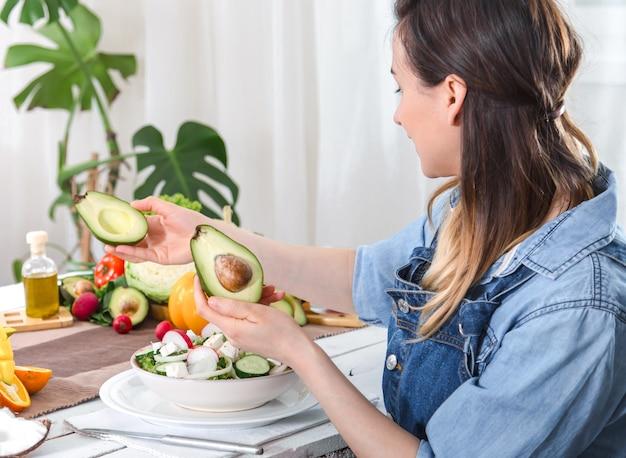 Junge und glückliche frau, die die avocado am esstisch betrachtet