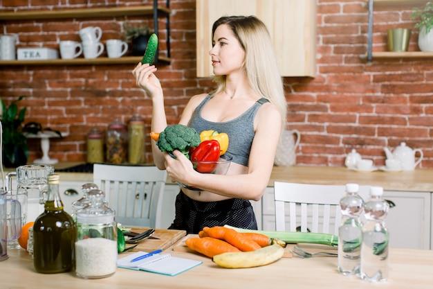 Junge und glückliche frau, die frech gurke und schüssel mit frischem gesundem gemüse hält, das auf dem tisch mit reis, olivenöl, karotte, banane und wasserflaschen drinnen in der küche steht