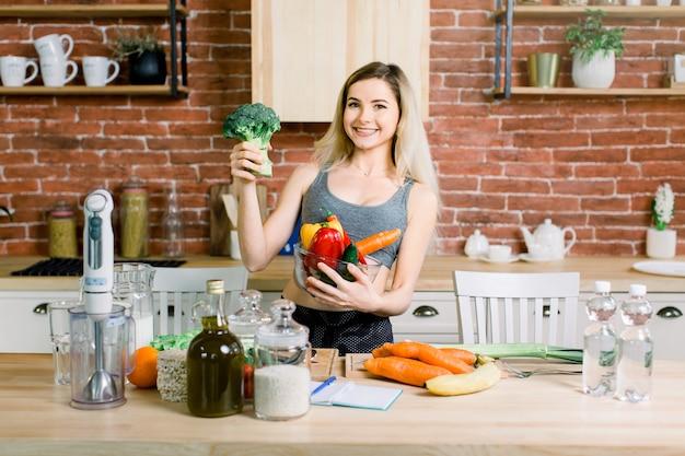 Junge und glückliche frau, die glasschale mit frischem gemüse in der linken hand und brokkoli in der rechten hand hält, während auf dem tisch mit gesundem essen in der modernen küche steht. gesundes lebensmittelkonzept