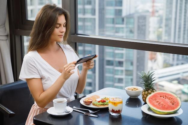 Junge und glückliche frau, die ihr köstliches frühstück fotografiert