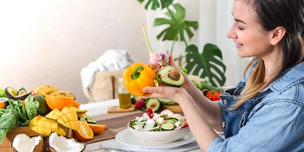 Junge und glückliche frau, die salat am tisch isst