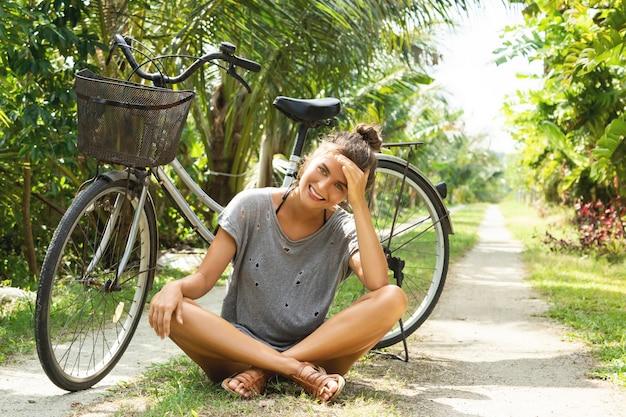 Junge und glückliche frau mit fahrrad im tropischen garten