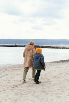 Junge und großmutter am strand voller schuss