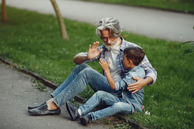 Junge und großvater gehen im park spazieren. alter mann, der mit enkel spielt. familie sitzt auf einem gras.