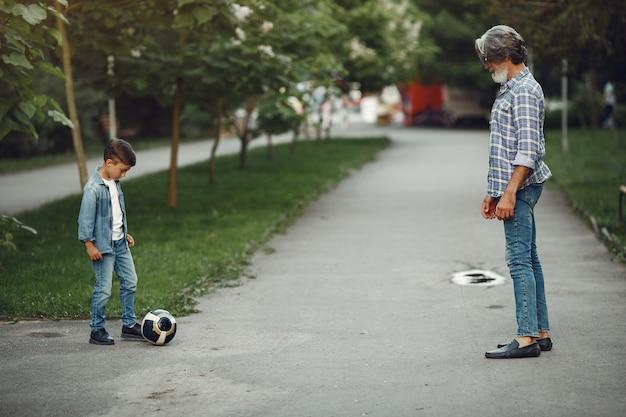 Junge und großvater gehen im park spazieren. alter mann, der mit enkel spielt. familie spielt mit einem ball.