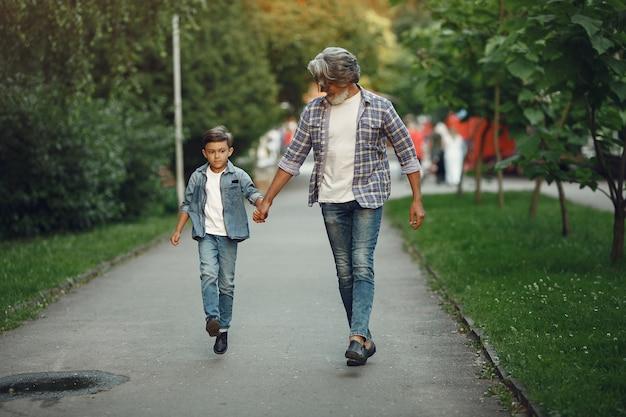 Junge und großvater gehen im park spazieren. alter mann, der mit enkel spielt.