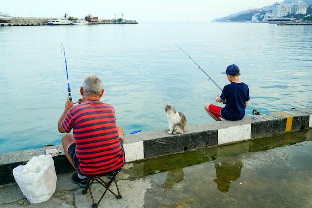 Junge und großvater mit angelruten, die vom pier im meer fischen.