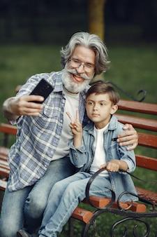 Junge und großvater sitzen auf einer bank. familie im park. alter mann, der mit enkel spielt. großvater benutzt ein telefon.