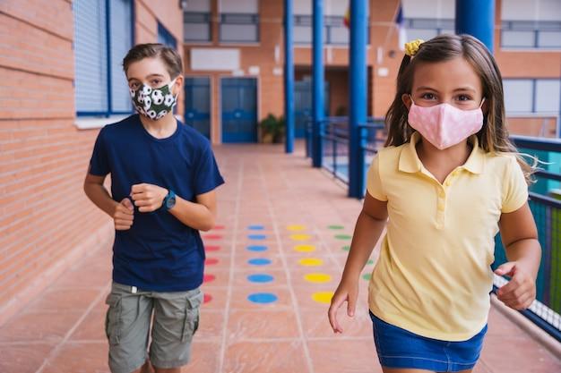 Junge und kleines mädchen, die im schulhof mit gesichtsmaske während der covid-pandemie laufen. zurück zur schule während der covid-pandemie