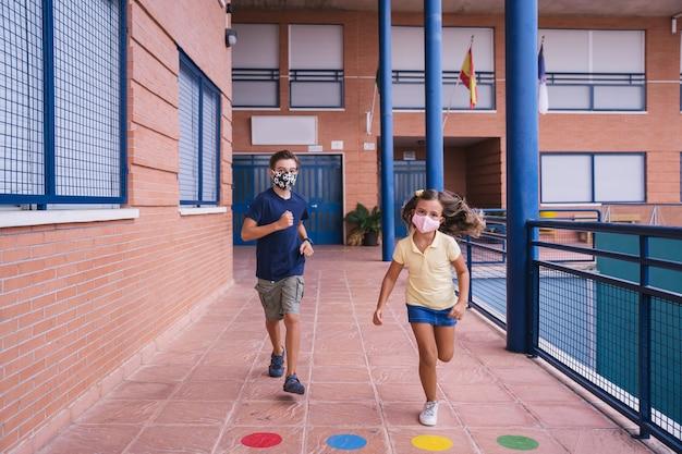 Junge und kleines mädchen, die im schulhof mit gesichtsmaske während der covid-pandemie laufen