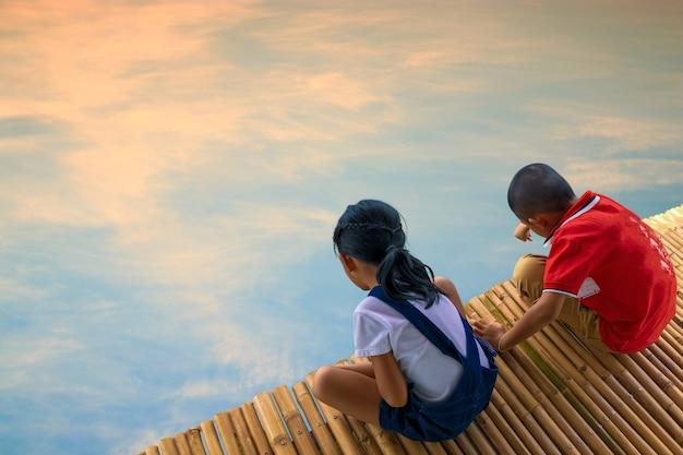 Junge und mädchen auf bambusbrücke und himmel