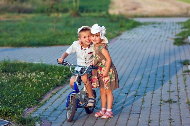Junge und mädchen auf dem fahrrad, das draußen an einem sonnigen tag des sommers spielt