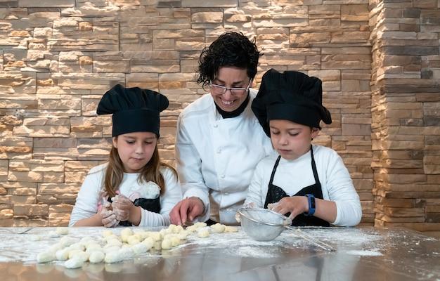 Junge und mädchen bereiten gnocchi in einem kochworkshop mit dem lehrer zu