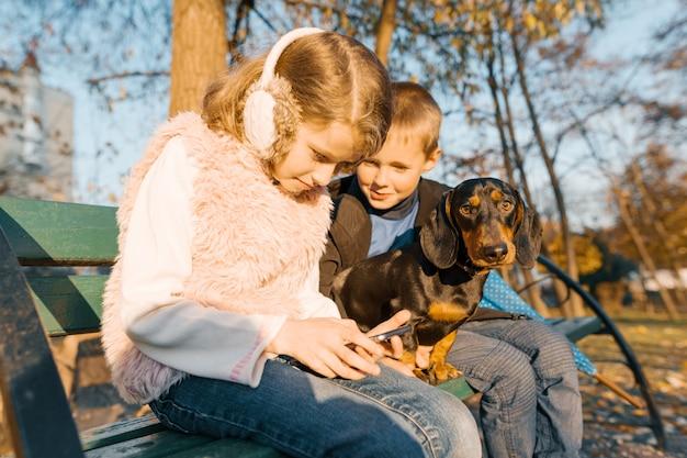 Junge und mädchen, die auf bank im park mit hund sitzen