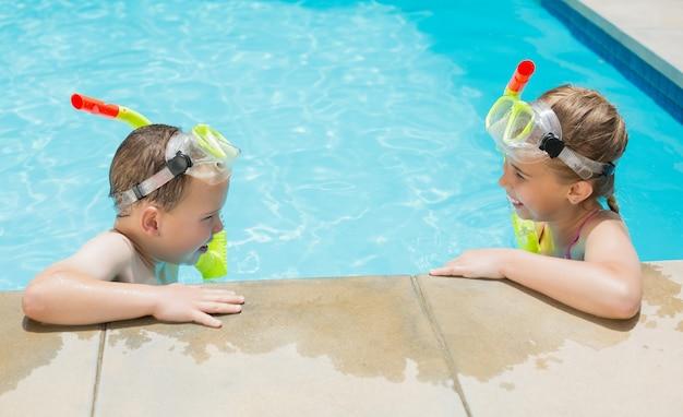 Junge und mädchen, die auf der seite des schwimmbades entspannen