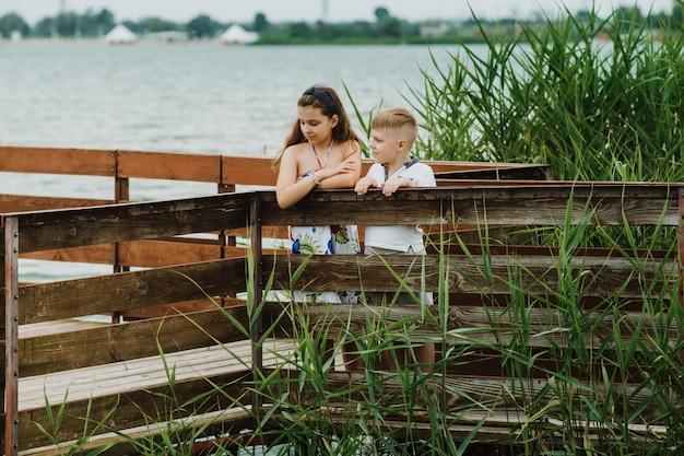 Junge und mädchen, die auf einem hölzernen pier auf einem seeufer stehen. sommerurlaub