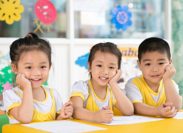 Junge und mädchen, die im kindergarten sitzen