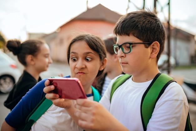Junge und mädchen, die intelligentes telefon auf einem weg von der schule verwenden