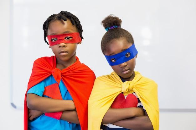 Junge und mädchen, die vortäuschen, ein superheld zu sein