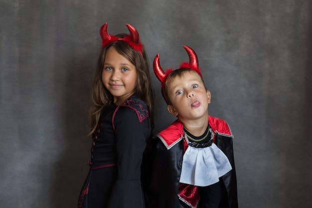 Junge und mädchen im halloween-kostüm auf grauer wand