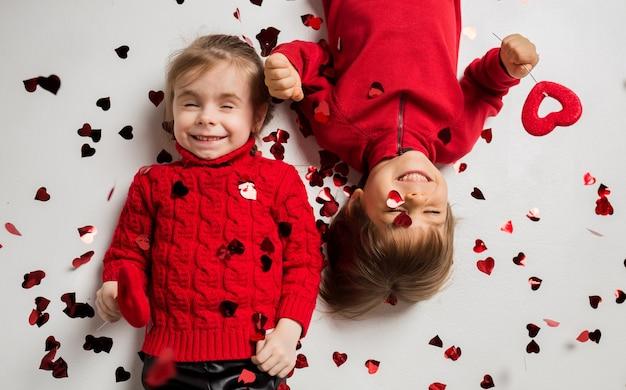 Junge und mädchen lügen und halten rote herzen auf weißem hintergrund mit konfetti