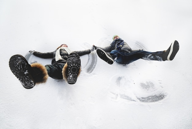 Junge und mädchen machen schneeengel