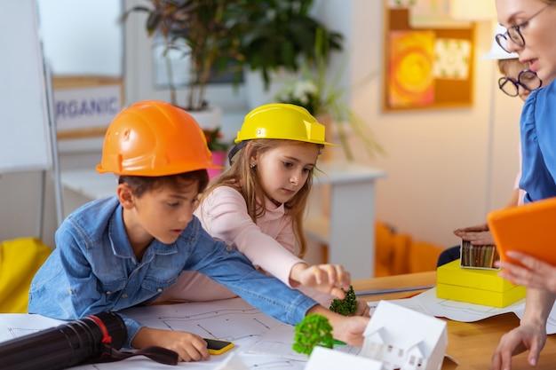 Junge und mädchen. schüler fühlen sich beim bauen und modellieren einer intelligenten stadt in der nähe des lehrers glücklich