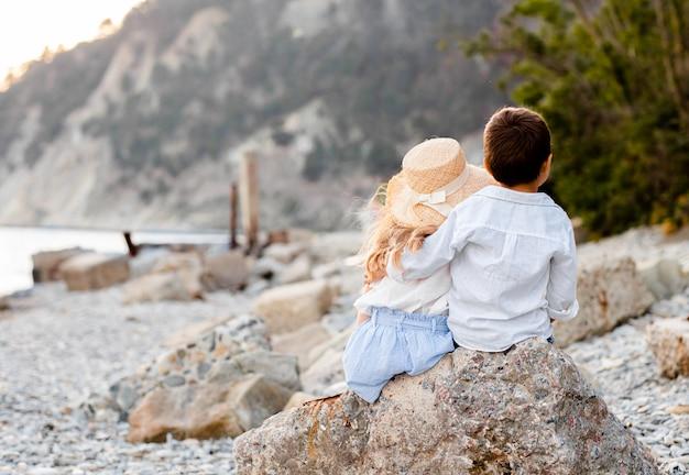 Junge und mädchen sitzen auf einem stein am strand