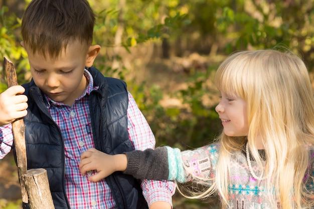 Junge und mädchen spielen im herbst zusammen mit stick im freien