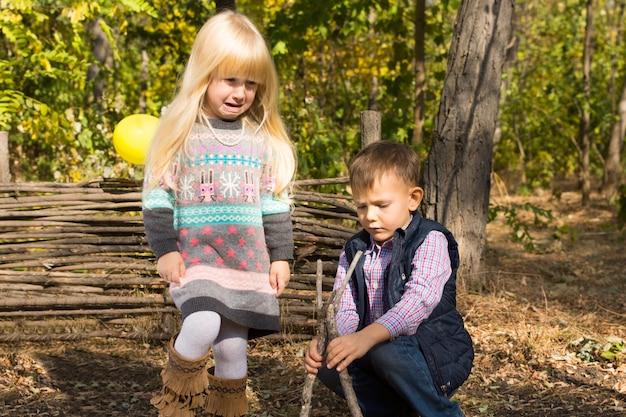 Junge und mädchen spielen zusammen im freien im wald und bauen ein kleines hölzernes wigwam aus zweigen und ästen, während sie einen unbeschwerten tag in der natur genießen