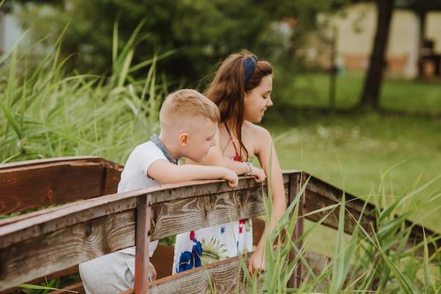 Junge und mädchen stehen auf einem hölzernen pier, sommerferien