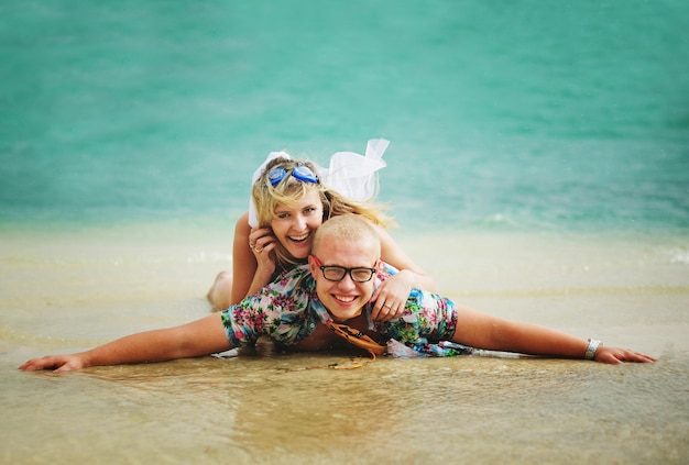 Junge und mädchen tummeln sich am strand auf einem hintergrund von blauem wasser