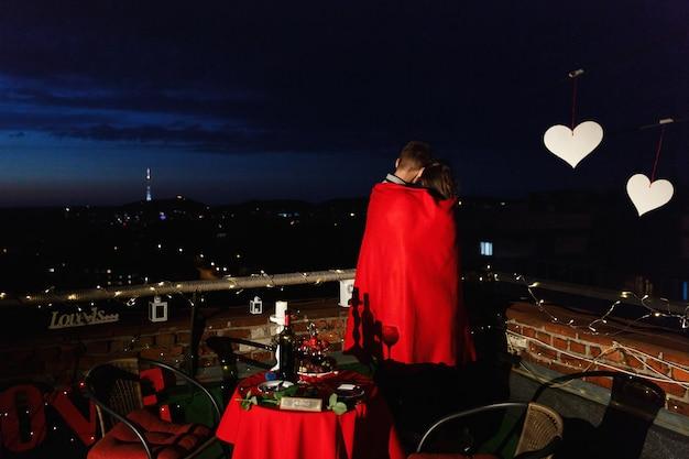 Junge und mädchen umarmen sich zarte stehend auf der dachspitze in den strahlen der abendlichter