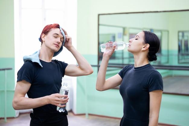 Junge und mädchentänzer trinken wasser und entspannen sich nach dem training