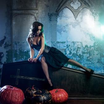 Junge und reizvolle frau, bild der hexen in einem kirchhof, der auf deckelsarg sitzt.