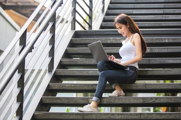 Junge und schöne asiatische frau, die mit ihrem laptop beim sitzen auf den jobstepps arbeitet