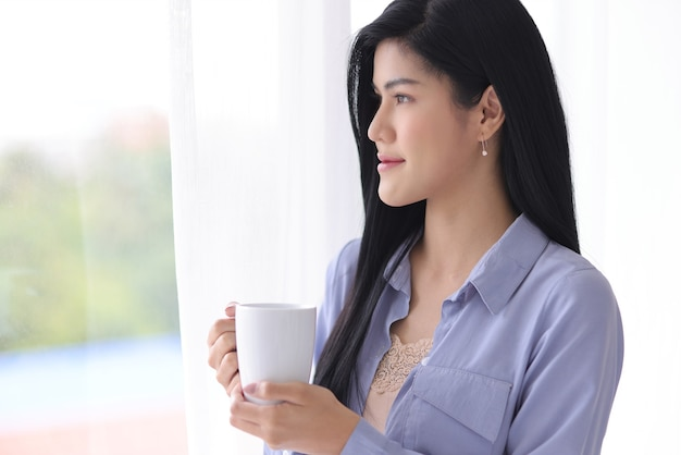Junge und schöne asiatische frau, die weiße keramische kaffeetasse mit entspannung und leichter geste hält, während weit nach außen mit weichem vorhang schauen. idee für eine glückliche morgenzeit.