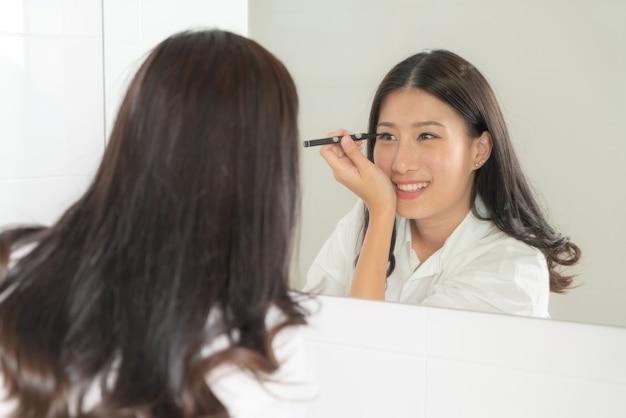 Junge und schöne asiatische frau machen sich spiegel
