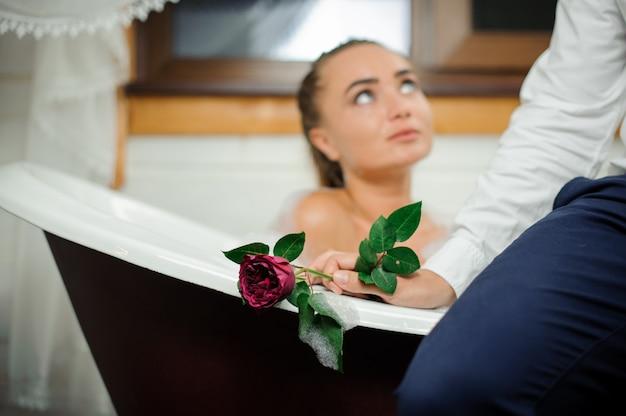 Junge und schöne frau, die im bad sich entspannt und mann betrachtet