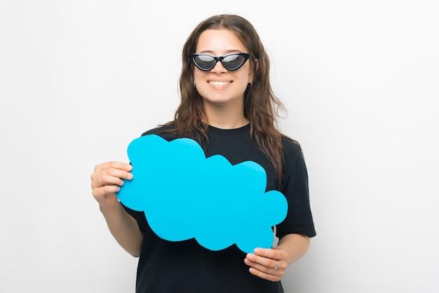 Junge und schöne frau hält eine blaue papierwolke wie eine sprechblase.