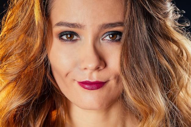 Junge und schöne frau, kurze haare, lockiges haar und abendliches metallisches make-up, perfekte haut, rote lippen, studioaufnahme auf schwarzem hintergrund. modemodell sinnlicher look