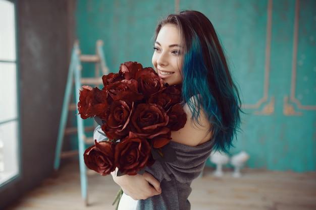 Junge und schöne frau mit strauß rosen