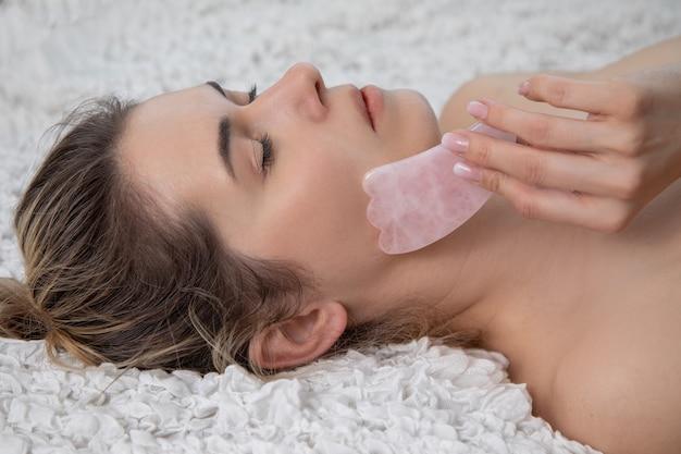 Junge und schöne frau während der traditionellen chinesischen massage - gua sha mit rosa stein. schönheitsbehandlung im spa-salon. anti-aging-hautpflege