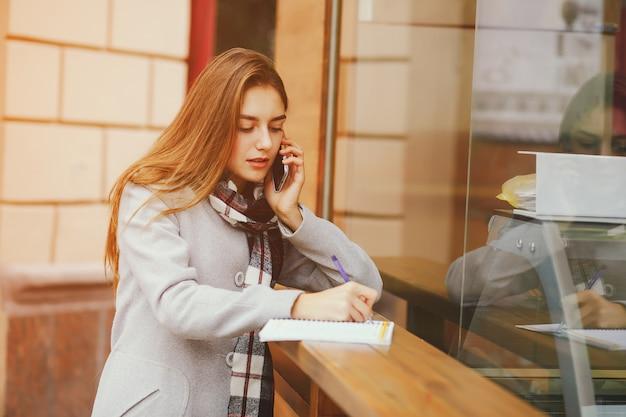 Junge und schöne gilr, die nahe gebäude in einer stadt stehen und das telefon verwenden