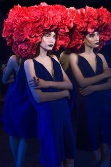 Junge und schöne kaukasische frau, die am spiegel im halloween-kleid mit rotem seltsamem hut und hexen-make-up steht.