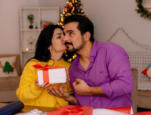 Junge und schöne paarfrau, die ein geschenk homding und ihren freund im weihnachtlich geschmückten raum mit weihnachtsbaum im hintergrund küsst