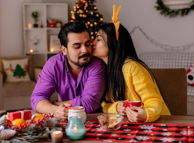 Junge und schöne paarfrau, die mann küsst, der am tisch mit tassen tee glücklich in der liebe in weihnachtlich geschmücktem raum mit weihnachtsbaum im hintergrund sitzt